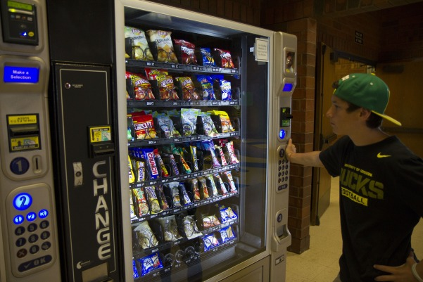 Junior Joe Nino explores his choices at the vending machine, which have changed in size, prize, and type, as a result of the new district policy pushing for better eating habits among students.