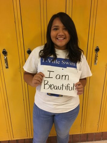 Student holds up sign saying she's beautiful in the way she is.