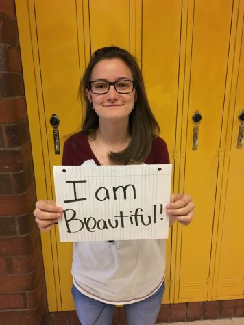 Brianna Merila embraces herself by standing proudly.