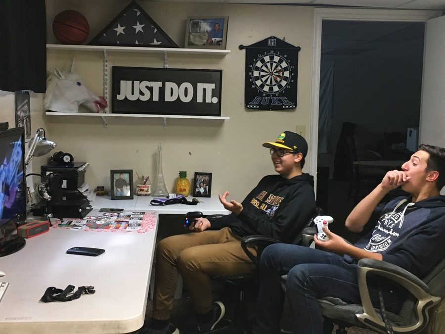 A pair of friends enjoy a video game together via couch play rather than through the online services.