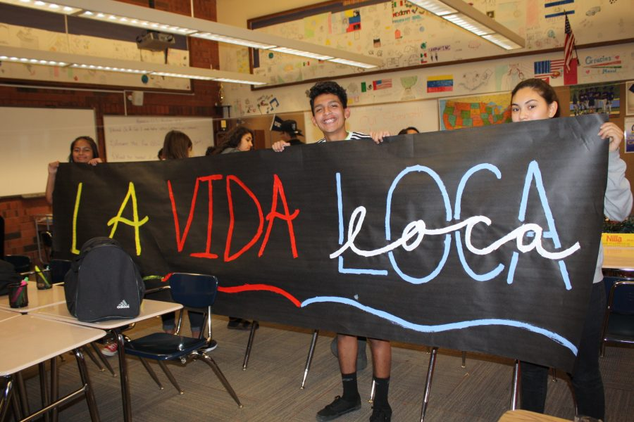 Latinos+in+Action+students+hold+up+a+banner+made+for+the+annual+LIA+dance.