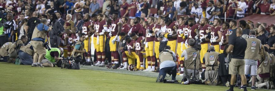 Washington+Redskins+players+link+arms+during+the+national+anthem+as+a+show+of+protest+following+the+president%27s+speech.