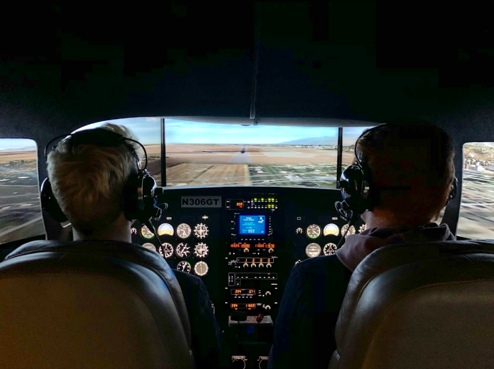 Two GTI students prepare for touchdown at Salt Lake City International Airport inside the school's advanced simulator.