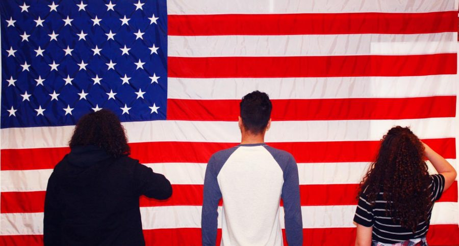 Students+stand+in+front+of+a+flag%2C+some+saluting+and+some+not%2C+to+represent+the+decision+students+make+to+either+stand+and+recite+the+pledge+of+allegiance+or+to+stand+in+silence.