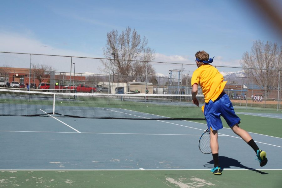 Junior, Jessie Marchant partices his serves at the tennis courts located on the East side of the school for an upcoming tennis match