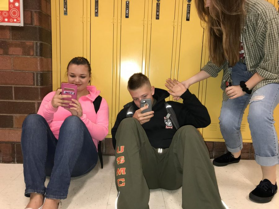 These+students+sit+in+the+hallway+on+their+phones%2C+texting+instead+of+interacting+with+one+another.+