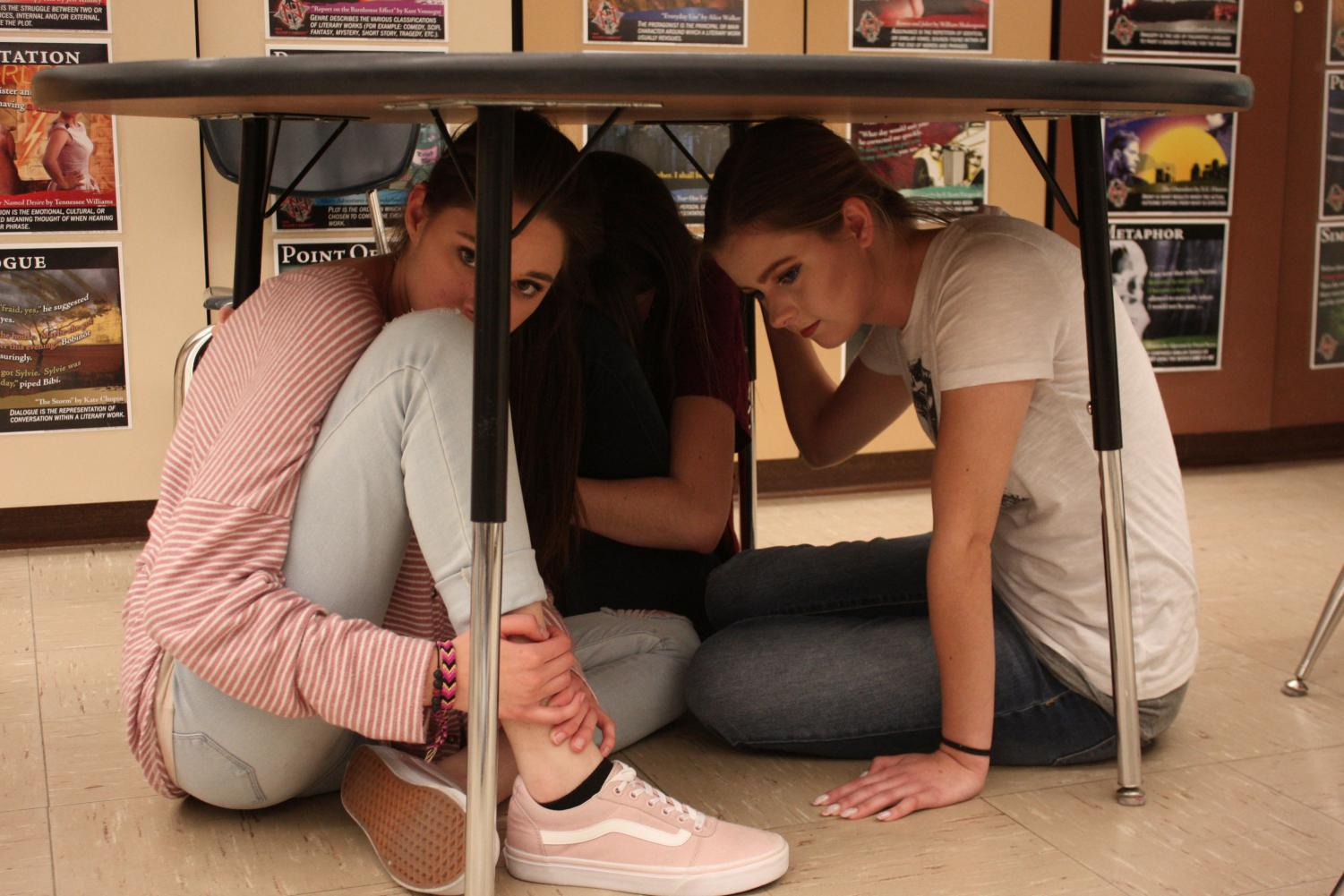 Students crouch under desk to simulate potential active shooter drill.