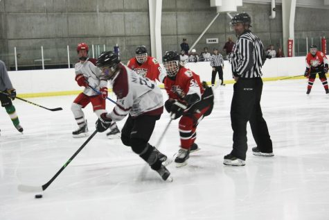 During a recent game, Ian Murray, #24 of the Oquirrh Mountaineers, defends the puck from Uinta Utes' #55 Owen Nash