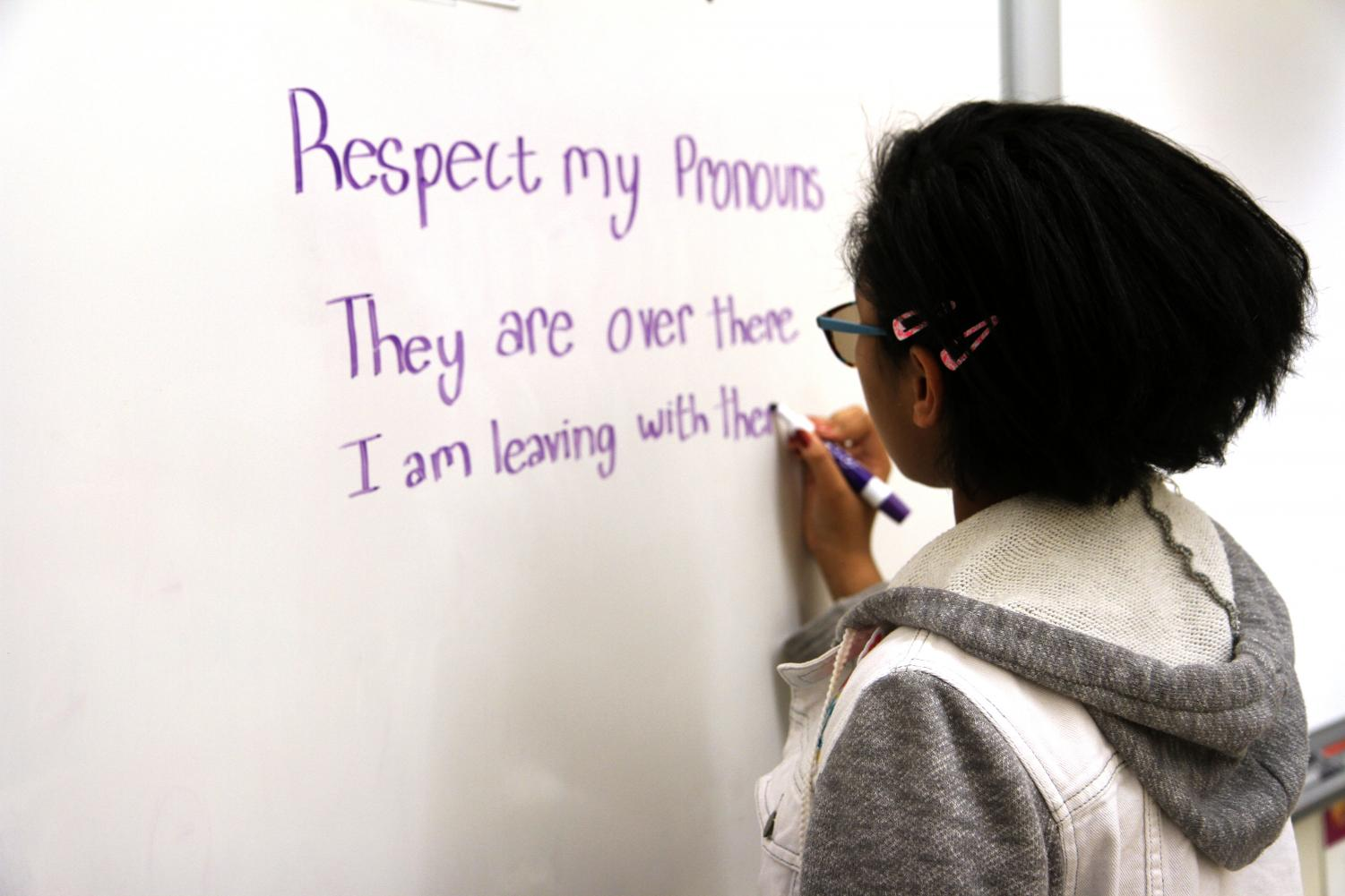 Non-binary sophomore Lia Lynn writes their pronouns on the board, demonstrating sentences in which their pronouns can be used. Oftentimes, students are told their pronouns are not grammatically correct. this, however, is a fallacy.