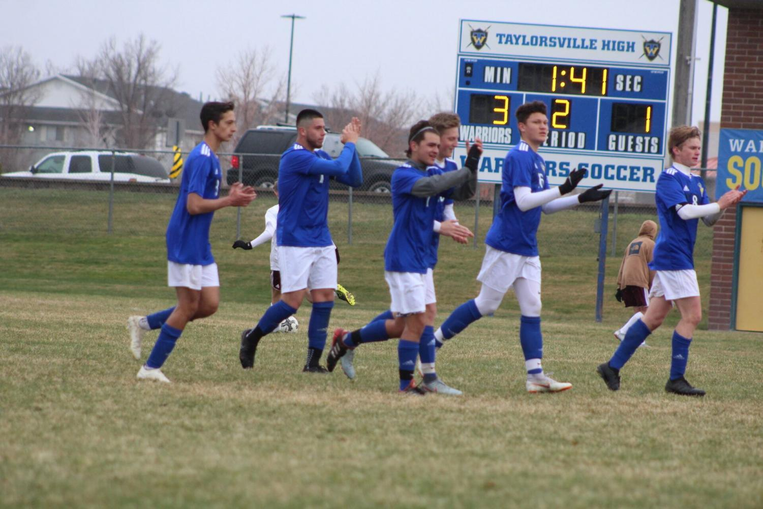 The Taylorsville Warrior, Boys Soccer Team cheering for their teammate at a home game.