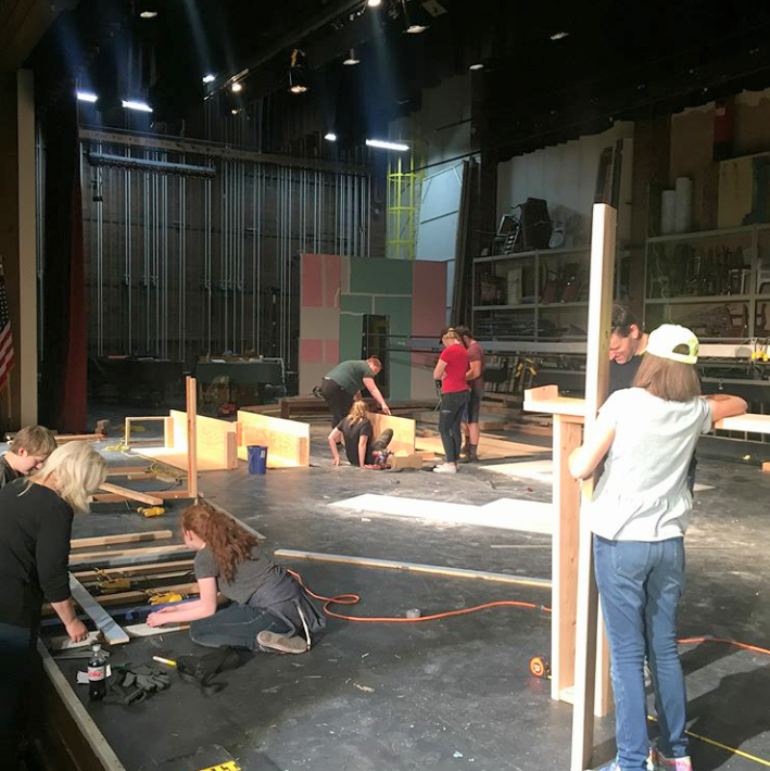 The stage crew works on building a set for the school musical,