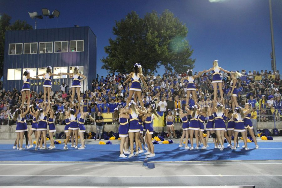 Cheerleaders lifting each other up during a cheer performance at a football game.