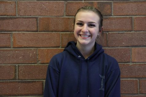 Senior Suzanne Buttenob posed against a brick background for her headshot