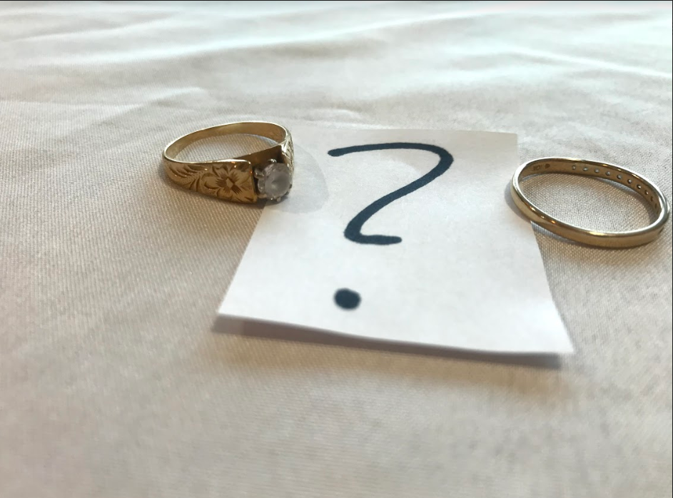 A man and woman's golden wedding rings sit across from each other and between them, a black, bold question mark.