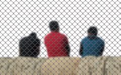 Three men sit behind a fence in order to symbolize deportation.