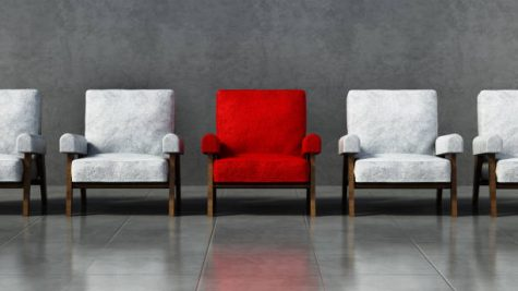 A red chair stands out among a line of white chairs.