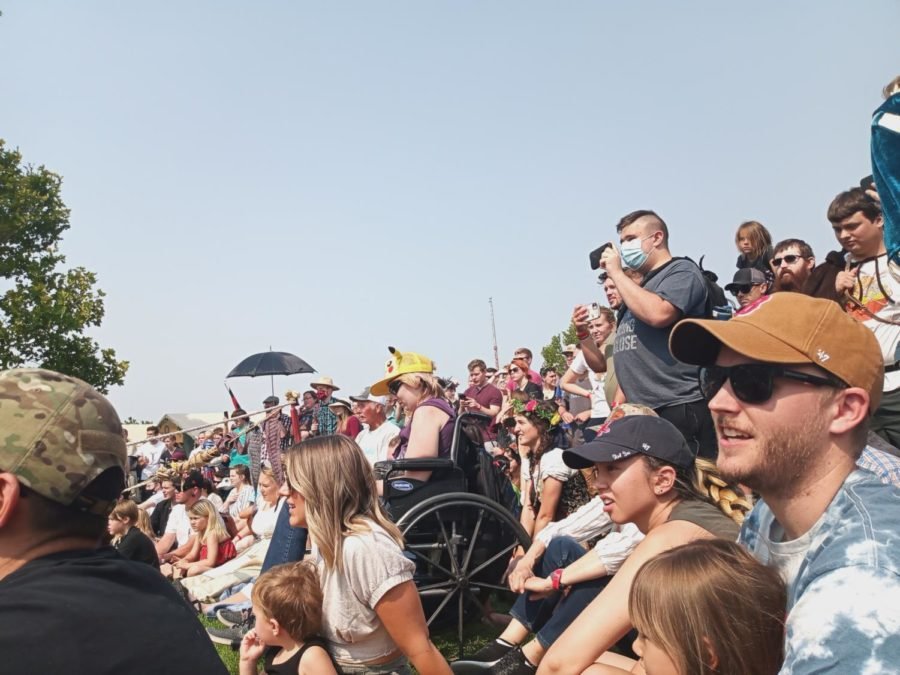 A crowd of people watching a show. Some are sitting on the ground and some are standing up.